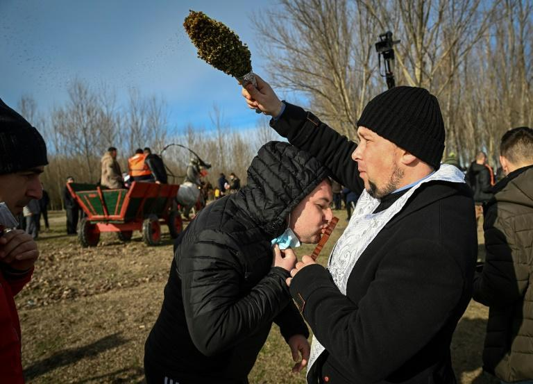 In Romania, priests splashed holy water on believers