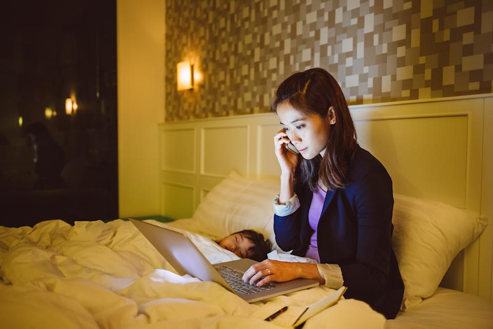 Pretty young mom talking on the phone while working with the laptop on the bed with little girl sleeping soundly beside her