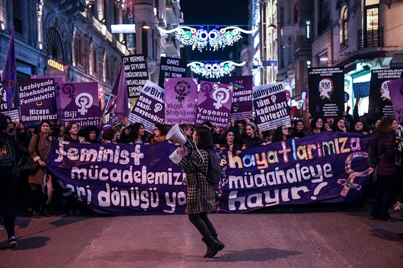 People hold signs as they march down Istiklal Avenue during a feminist night march to mark International Women's Day in Istanbul on March 8, 2017