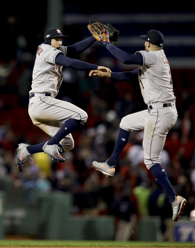 Houston Astros center fielder George Springer, left, and shortstop Carlos Correa celebrate their win -against the Boston Red Sox in Game 1 of a baseball American League Championship Series on Saturday, Oct. 13, 2018, in Boston. The Astros won 7-2. (AP Photo/Charles Krupa)