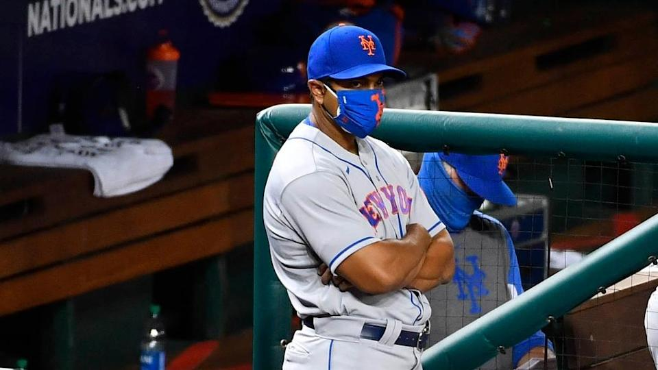 Luis Rojas stares from dugout with mask during game