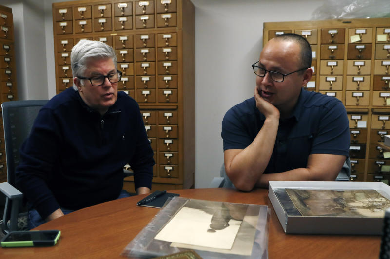 In this Thursday, Nov. 14, 2019 photo, Eric Hemenway, right, the director of archives and records for the Little Traverse Bay Band of Odawa Indians talks with collector Richard Port Jr., at the University of Michigan William Clements Library in Ann Arbor, Mich. Hemenway was examining the photographs acquired by the library in 2016 from Pohrt Jr. which represent some 80 indigenous groups. (AP Photo/Carlos Osorio)