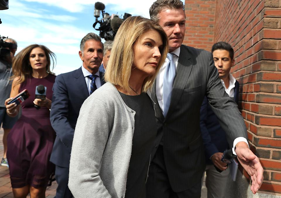 BOSTON, MA - AUGUST 27: Lori Loughlin and her husband Mossimo Giannulli, behind her at left, leave the John Joseph Moakley United States Courthouse in Boston on Aug. 27, 2019. A judge says actress Lori Loughlin and her fashion designer husband, Mossimo Giannulli, can continue using a law firm that recently represented the University of Southern California. The couple appeared in Boston federal court on Tuesday to settle a dispute over their choice of lawyers in a sweeping college admissions bribery case. Prosecutors had said their lawyers pose a potential conflict of interest. Loughlin and Giannulli say the firms work for USC was unrelated to the admissions case and was handled by different lawyers. (Photo by John Tlumacki/The Boston Globe via Getty Images)