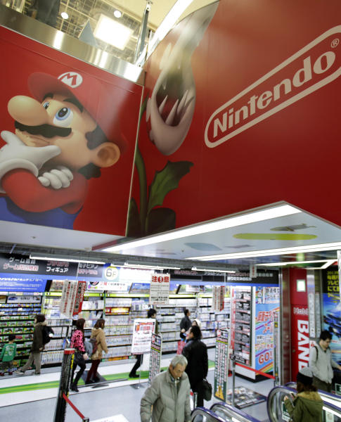 In this photo taken Sunday, Dec. 15, 2013, shoppers walk under the logo of Nintendo and Super Mario characters at an electronics store in Tokyo. This holiday season Nintendo faces a critical test with its Wii U video game console that is pitted against Sony's PlayStation 4 and Microsoft's Xbox One as it seeks to revive flagging sales. (AP Photo/Shizuo Kambayashi)