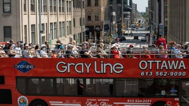 People ride a tourist bus through downtown Ottawa earlier this summer during the COVID-19 pandemic. (Brian Morris/CBC - image credit)