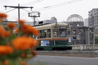 A running tram is seen near the Atomic Bomb Dome in Hiroshima, western Japan, Monday, Aug. 3, 2020. A tram which survived the Hiroshima atomic bombing will run, without any passenger, on the streets on Aug. 6 to commemorate the day of atomic bombing in the city. (AP Photo/Eugene Hoshiko)