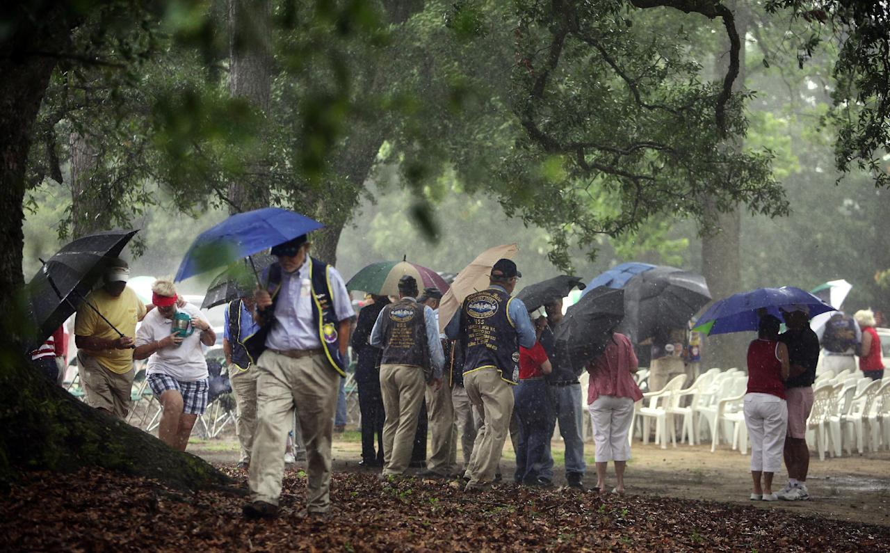 People attending the American Legion Post 21 Memorial Day observance head for cover just as the event was about to begin when rain from outer bands of Tropical Depression Beryl passed through the Summerville, S.C., area Monday, May 28, 2012. Organizers quickly elected to cancel the observance due to the inclement weather. (AP Photo/The Post and Courier, Brad Nettles) NO SALES; MAGS OUT