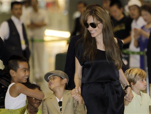 "U.S. actress Angelina Jolie, second from right, and her children from left, 8-year-old Maddox, Zahara Marley, 6, partially hidden behind Maddox, Pax Thien, 6, and Shiloh Nouvel, 4, arrive at Narita International Airport in Narita near Tokyo Monday, July 26, 2010 for the Japan premiere of her spy action-thriller film ""Salt."" (AP Photo/Koji Sasahara)"