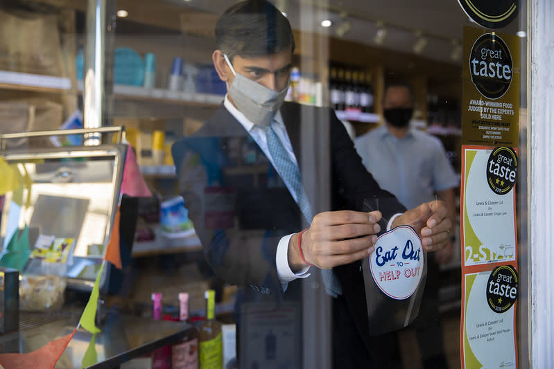The Chancellor Rishi Sunak helps to advertise Eat Out To Help Out by putting up stickers in participating restaurants and cafes in Northallerton