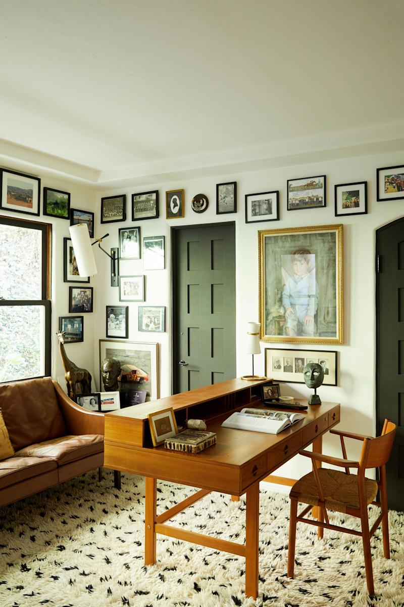"""One of the coziest and most personal rooms in the house is the office, covered with a collection of family photos and a portrait of Bennett as a three-year-old. The bronze giraffe in the back corner, as well as the bust next to it, were made by his grandmother, who was a sculptor. """"I lost my family when I was too young,"""" he says. """"This room has so many memories."""" The leather sofa is a vintage piece by Borge Mogensen, and the Danish teak desk is by Jens Quistgaard."""