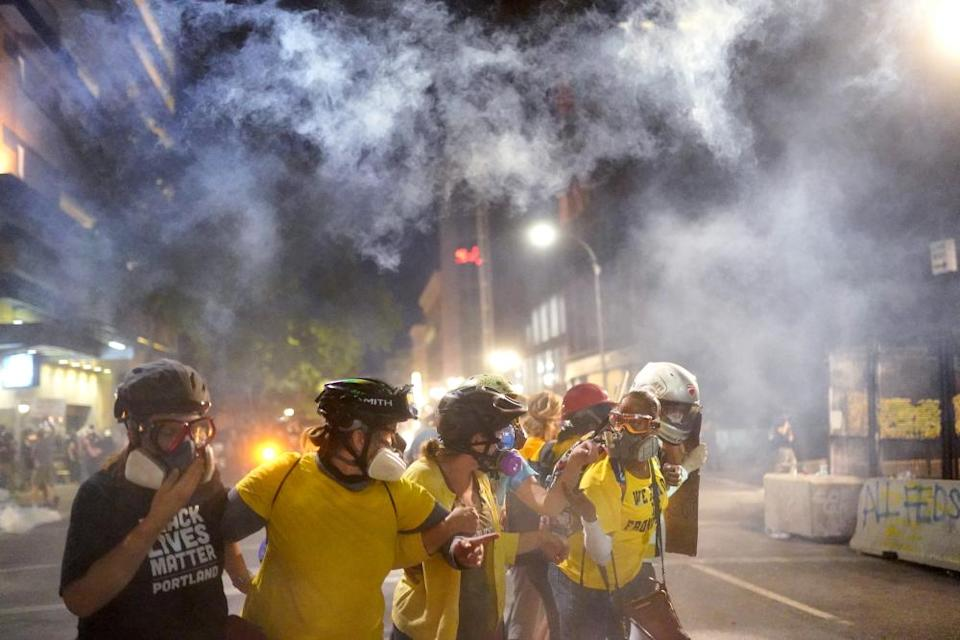 Members of Moms United for Black Lives Matter hold their ground as federal officers fire tear gas into a protest on July 29, 2020 in Portland, Oregon.