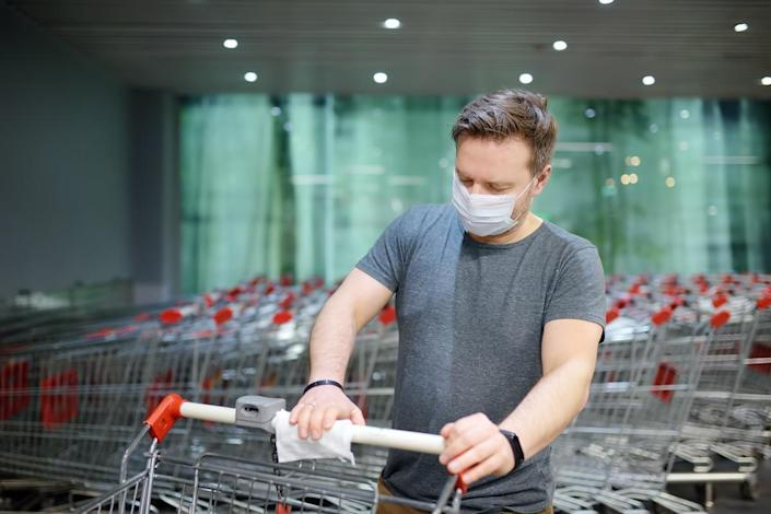 Man wearing disposable medical face mask wipes the shopping cart handle with a disinfecting cloth in grocery store