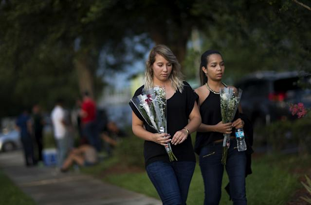 <p>Mourners carry flowers into the visitation for Pulse nightclub shooting victim Javier Jorge-Reyes, in Orlando. (Photo: David Goldman/AP) </p>