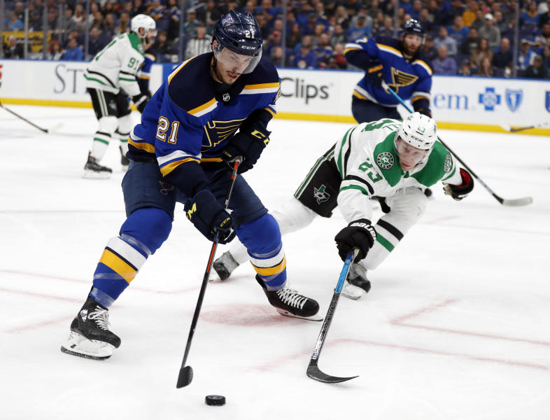 St. Louis Blues center Tyler Bozak (21) is challenged by Dallas Stars' Esa Lindell (23) for control of the puck during the second period in Game 1 of an NHL second-round hockey playoff series Thursday, April 25, 2019, in St. Louis. (AP Photo/Jeff Roberson)