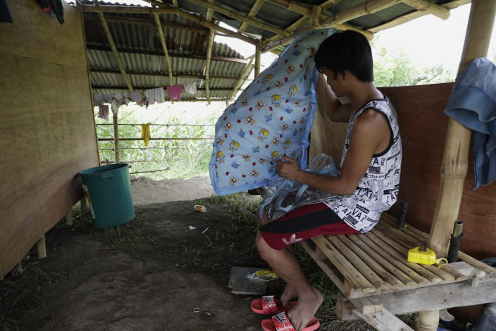 Ronnel Manjares looks at a small bed that was donated for their baby Kobe at their house in Tanauan, Batangas province, Philippines on Wednesday, July 15, 2020. His 16-day-old son Kobe was heralded as the country's youngest COVID-19 survivor. But the relief and joy proved didn't last. Three days later, Kobe died on June 4 from complications of Hirschsprung disease, a rare birth defect. (AP Photo/Aaron Favila)