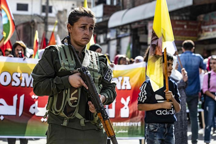 A members of the Kurdish Internal Security Police Force of Asayesh stands guard as Syrian Kurds demonstrate against Turkish threats to launch a military operation on their region, in the town of Al-Qahtaniyah, in northeastern Syrian Al-Hasakah Governorate on Oct. 7, 2019. -