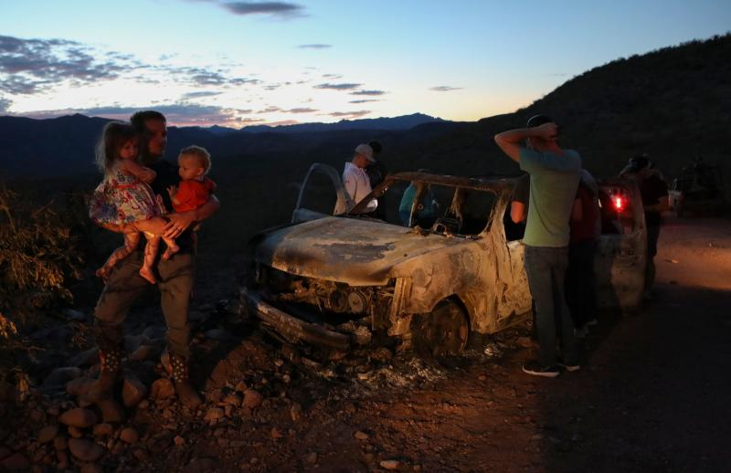"""Members of the LeBaron family look at the burned car where part of the nine murdered members of the family were killed and burned during an ambush in Bavispe, Sonora mountains, Mexico, on November 5, 2019. - US President Donald Trump offered on November 5 to help Mexico """"wage war"""" on its cartels after three women and six children from an American Mormon community were murdered in an area notorious for drug traffickers. (Photo by Herika MARTINEZ / AFP) / The erroneous mention appearing in the metadata of this photo has been modified in AFP systems in the following manner: byline should read [Herika MARTINEZ] instead of [STRINGER]. Please immediately remove the erroneous mention from all your online services and delete it from your servers. If you have been authorized by AFP to distribute it to third parties, please ensure that the same actions are carried out by them. Failure to promptly comply with these instructions will entail liability on your part for any continued or post notification usage. Therefore we thank you very much for all your attention and prompt action. We are sorry for the inconvenience this notification may cause and remain at your disposal for any further information you may require. (Photo by HERIKA MARTINEZ/AFP via Getty Images)"""