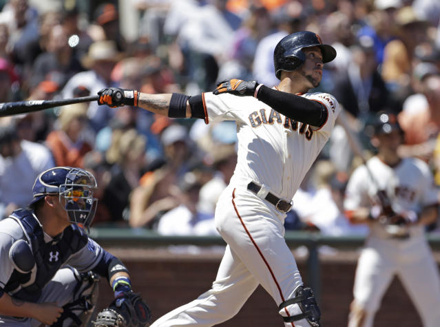 San Francisco Giants' Gregor Blanco, right, hits a two-RBI triple off San Diego Padres relief pitcher Luke Gregerson as Padres catcher Yasmani Grandal, left, looks on during the seventh inning of their baseball game on Wednesday, June 19, 2013, in San Francisco. (AP Photo/Eric Risberg)