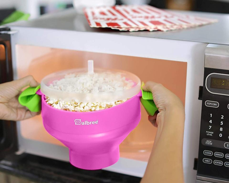 """You can pop movie theater-level corn while using up only a Frisbee's worth of valuable space since this doubles as a serving bowl. All you have to do is add generic kernels and whatever oils or butters you feel in your heart, and you'll be raring to go.<br /><br /><strong>Promising review:</strong>""""This is a fast, effective and low-cost means to prepare popcorn. I got tired of paying a premium for microwave popcorn packets at the grocery. I didn't want another appliance on my counter to air pop either.<strong>This was the perfect solution.</strong>I use inexpensive bulk popping corn, no oil or salt and I don't have to worry about the metal in the microwave popcorn bags that gets extremely hot and scorches the upside down paper plate I have to put under the microwave bag each time. Plus, weren't we told not to put anything metal in the microwave anyway? I pull the Salbree out, expand it and add a 1/4 cup of popping corn kernels in the base to the full line. I put it in the microwave for 3+ minutes and listen for the kernels to stop popping. Using the cool handles I lift it out of the microwave, give it a minute to cool and add just enough butter to give it flavor.<strong>Then I eat right out of the same bowl I cooked in.</strong>When done I dump out the few kernels that didn't pop.<strong>I wash it out with dish soap and hot water, let it dry and then put it away for next time.</strong>Economical, safe, less oil and salt and only one bowl to clean. No new appliance and no metal in the microwave. Pure genius. A great value."""" —<a href=""""https://www.amazon.com/gp/customer-reviews/R2XDAAT4TNV23N?ASIN=B01G7SGO2G&ie=UTF8&linkCode=ll2&tag=huffpost-bfsyndication-20&linkId=8c2fa74d265aad21ef56f18003c317eb&language=en_US&ref_=as_li_ss_tl"""" target=""""_blank"""" rel=""""noopener noreferrer"""">RobG</a><br /><br /><strong>Get it from Amazon for<a href=""""https://www.amazon.com/Original-Salbree-Microwave-Silicone-Collapsible/dp/B01G7SGO2G?&linkCode=ll1&tag=huffpost-bfsyndication-20&linkId=e51da1"""