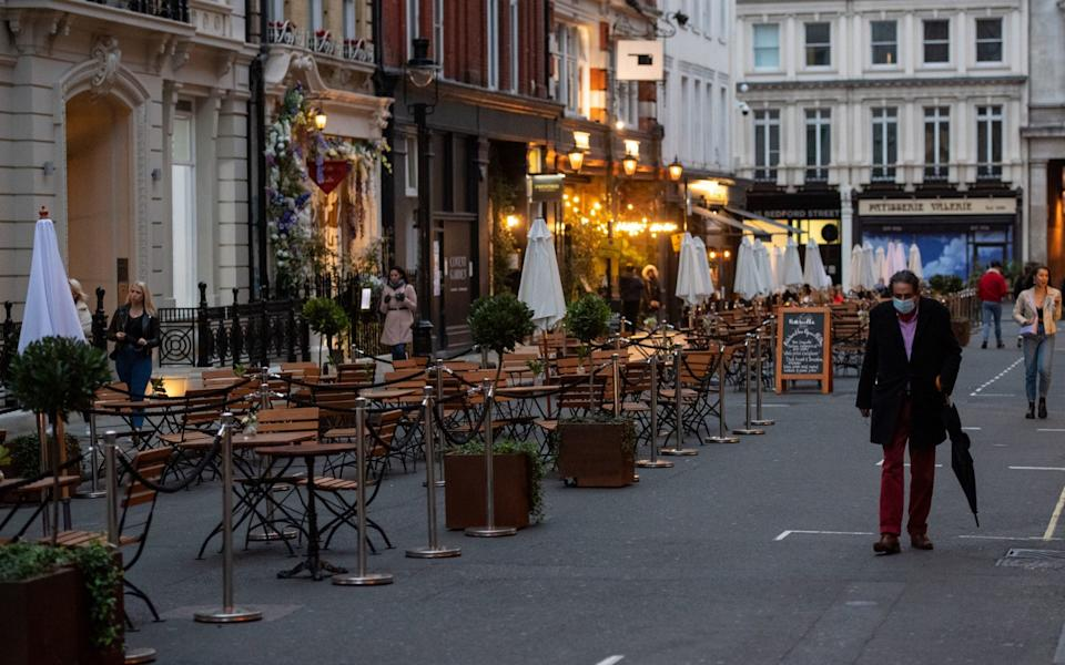 People pass empty tables outside a restaurant in Covent Garden, London, after the city was put into Tier 2 restrictions to curb the spread of coronavirus - Dominic Lipinski/PA Wire
