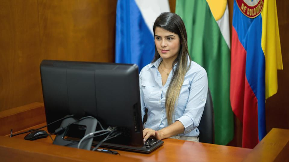 Portrait of a female clerk working at the courtroom typing the session - legal system technology concepts.
