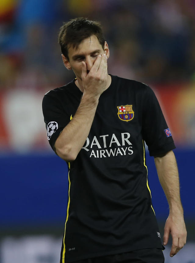 Barcelona's Lionel Messi covers his face during the Champions League quarterfinal second leg soccer match between Atletico Madrid and FC Barcelona at the Vicente Calderon stadium in Madrid, Spain, Wednesday, April 9, 2014. (AP Photo/Andres Kudacki)