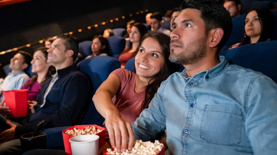 Portrait of a happy couple at the movies and woman stealing popcorn from her boyfriend - entertainment concepts.