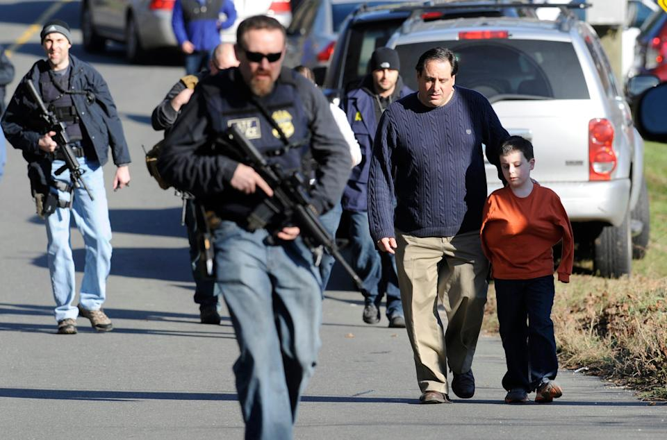 Parents leave a staging area after being reunited with their children following a shooting at the Sandy Hook Elementary School in Newtown, Conn., about 60 miles (96 kilometers) northeast of New York City, Friday, Dec. 14, 2012. An official with knowledge of Friday's shooting said 27 people were dead, including 18 children. It was the worst school shooting in the country's history. (AP Photo/Jessica Hill)