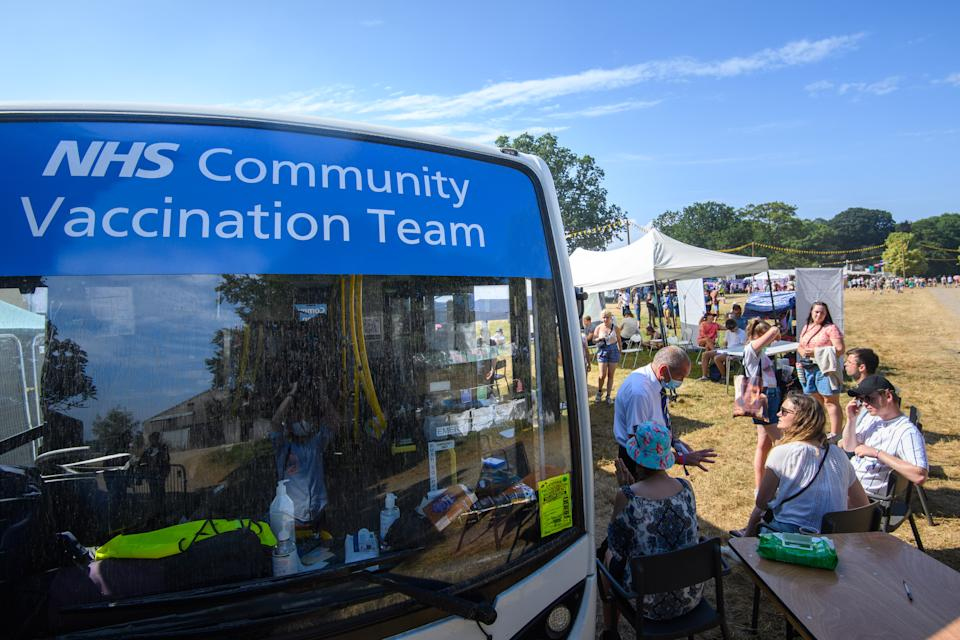 Festival goers queue for Coronavirus Vaccines, at an NHS community vaccination team bus, on the third day of the Latitude festival in Henham Park, Southwold, Suffolk. The walk-in service is a joint venture between Norfolk and Waverley CCG and GM graham pharmacies. Picture date: Sunday July 25, 2021. Photo credit should read: Matt Crossick/Empics
