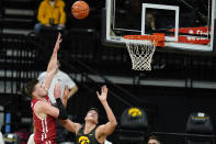 Wisconsin forward Micah Potter, left, shoots over Iowa center Luka Garza during the first half of an NCAA college basketball game, Sunday, March 7, 2021, in Iowa City, Iowa. (AP Photo/Charlie Neibergall)