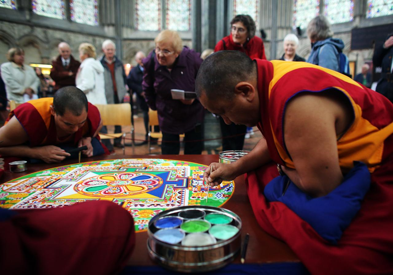 SALISBURY, ENGLAND - OCTOBER 03: People watch as Tibetan Monks from the Tashi Lhunpo Monastery, complete a Chenrezig Sand Mandala in Salisbury Cathedrals Chapter House on October 3, 2013 in Salisbury, England. The monks, who started the painstaking process of creating the sand mandela with millions of grains of coloured sand on Monday, will end it tomorrow in a destruction ceremony and procession to the River Avon. The monks who currently live in exile in India are visiting various places in the UK and Europe and will complete two more sand mandelas - which are an artistic tradition of Tibetan Buddhism and are a symbolic picture of the universe representing an imaginary palace - before returning home to their monastery in late November. (Photo by Matt Cardy/Getty Images)