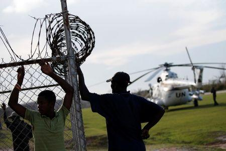 Men stand by a fence next to a United Nations helicopter at the airport after Hurricane Matthew passes Jeremie, Haiti, October 7, 2016. REUTERS/Carlos Garcia Rawlins