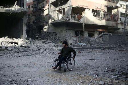 A man in a wheelchair is seen at a damaged site after an airstrike in the besieged town of Douma