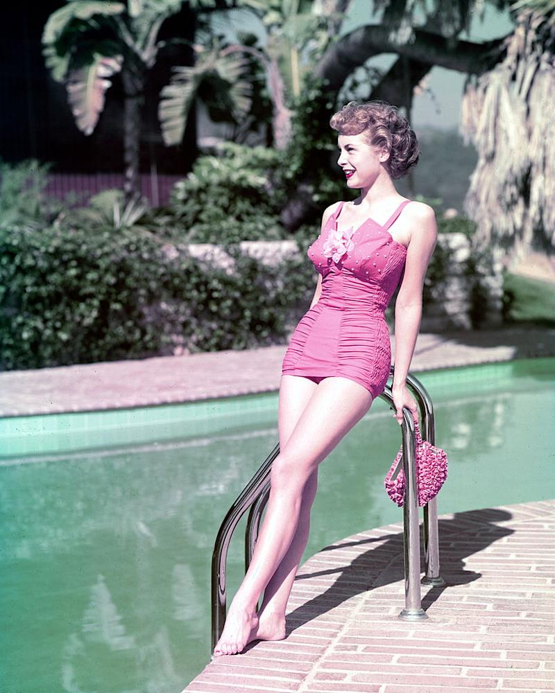 Full-length shot of Janet Leigh (1927-2004), US actress, wearing a pink swimsuit and leaning against the ladder at the edge of a swimming pool, circa 1950. (Photo by Silver Screen Collection/Getty Images)