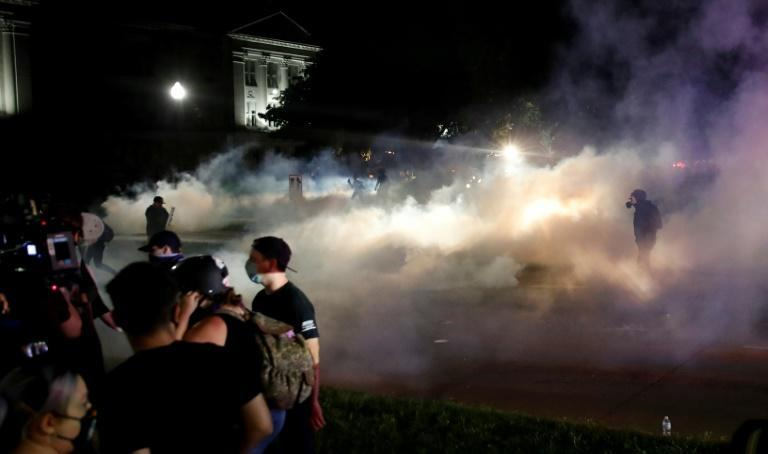 Protestors run for cover as police shoot teargas in an effort to disperse demonstrations against the shooting of Jacob Blake in Kenosha, Wisconsin on August 25, 2020