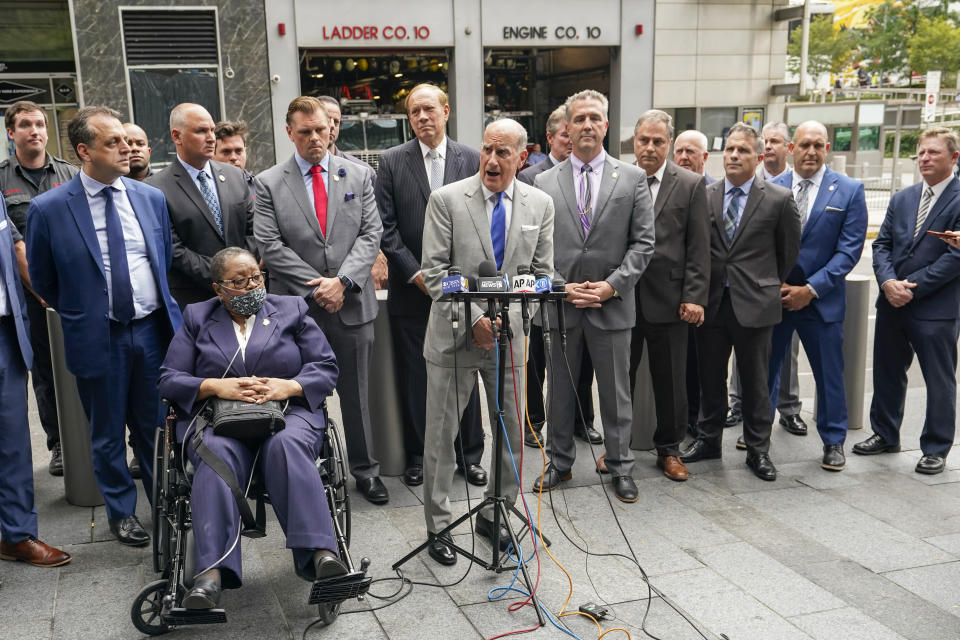 Retired NYPD Detective Barbara Burnette, foreground left, who worked on the World Trade Center pile for 23 days after the terrorist attacks in 2001 is joined by her attorney Nicholas Papain, center, and former New York Gov. George Pataki, background center, and other 9/11 first responders during a news conference, Wednesday, Sept. 8, 2021, in New York. Two decades after the collapse of the World Trade Center, people are still coming forward to report illnesses that might be related to toxic dust that billowed over the city after the terror attack. (AP Photo/Mary Altaffer)