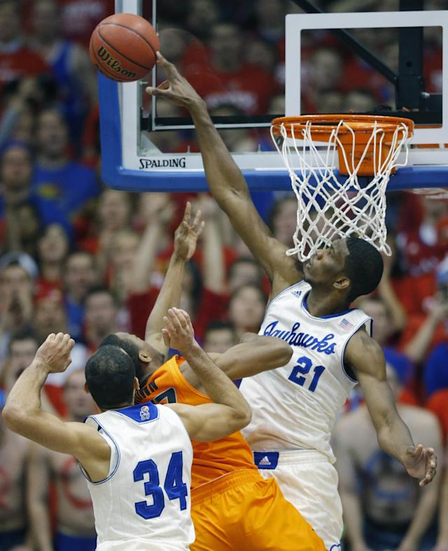 Kansas center Joel Embiid (21) blocks a shot by Oklahoma State guard Markel Brown (22) during the first half of an NCAA college basketball game at Allen Fieldhouse in Lawrence, Kan., Saturday, Jan. 18, 2014. (AP Photo/Orlin Wagner)