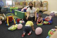 This May 4, 2021 image shows teacher Graciela Olague-Barrios working with two infants at Cuidando Los Ninos in Albuquerque, N.M. The charity provides housing, child care and financial counseling for mothers, all of whom will benefit from expanded Child Tax Credit payments that will start flowing in July to roughly 39 million households. (AP Photo/Susan Montoya Bryan)