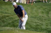 Dustin Johnson chips to the green on the ninth hole during the first round of the The Players Championship golf tournament Thursday, March 11, 2021, in Ponte Vedra Beach, Fla. (AP Photo/John Raoux)
