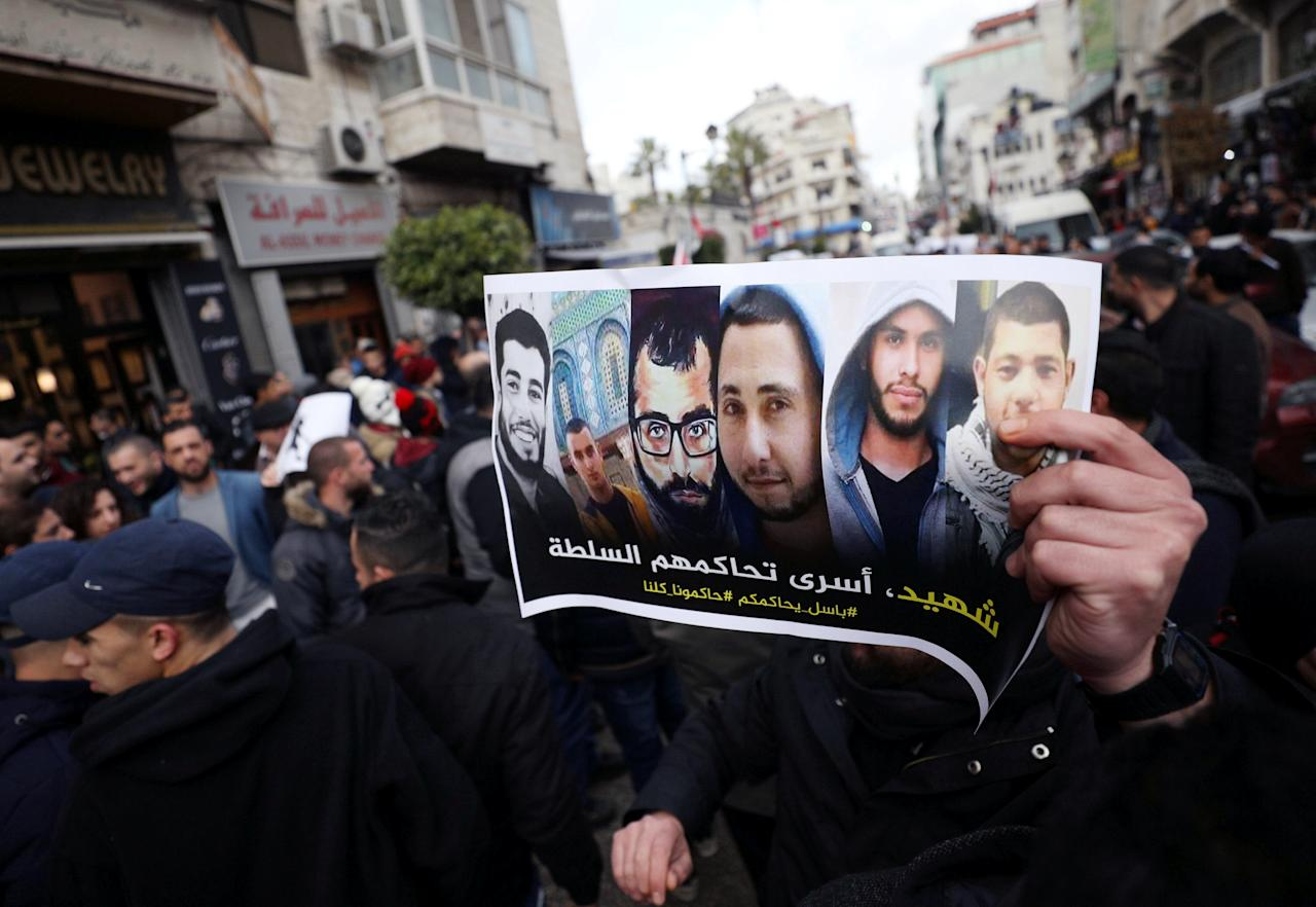"""A Palestinian holds a poster that reads, """"A martyr and prisoners prosecuted by the authority"""" during a protest against the Palestinian authority, in the West Bank city of Ramallah, March 13, 2017. REUTERS/Mohamad Torokman"""