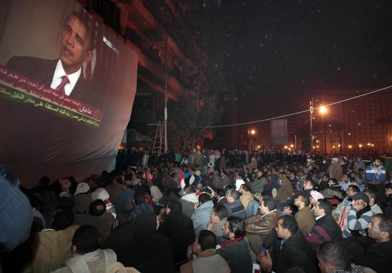 Egyptian anti-government protesters gathered in Tahrir (Liberation) square, watch a screen showing U.S. President Barack Obama live on a TV broadcast from Washington DC, speaking about the situation in Egypt, early Wednesday, Feb. 2, 2011. (AP Photo/Lefteris Pitarakis)