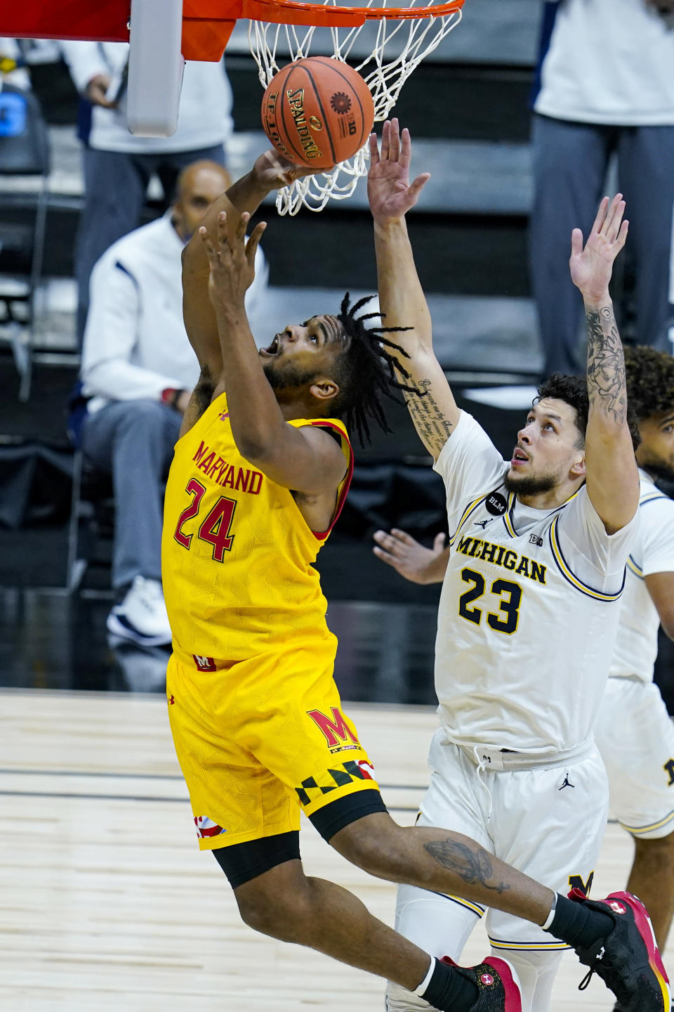 Maryland forward Donta Scott (24) shoots in front of Michigan forward Brandon Johns Jr. (23) in the first half of an NCAA college basketball game at the Big Ten Conference tournament in Indianapolis, Friday, March 12, 2021. (AP Photo/Michael Conroy)