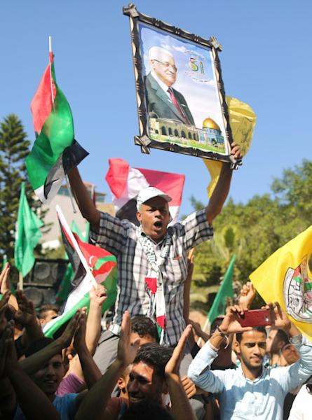 A man holds a portrait of the Palestinian president among Palestinians waving flags as they gather in Gaza City to celebrate after rival Palestinian factions Hamas and Fatah reached an agreement on ending a decade-long split on October 12, 2017