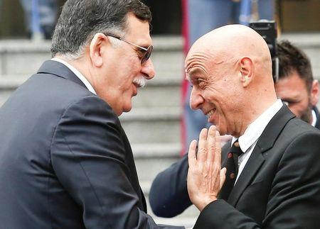 Faiez Mustafa Serraj, President of the Presidency Council of the Government of National Accord of Libya (L), is greeted by Italian Interior Minister Marco Minniti during a meeting in Rome, Italy March 20, 2017. REUTERS/Remo Casilli