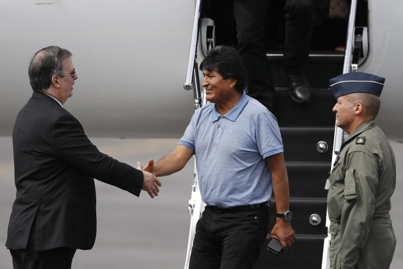 Mexican Foreign Minister Marcelo Ebrard, left, welcomes former Bolivian President Evo Morales in Mexico City, Tuesday, Nov. 12, 2019. Mexico granted asylum to Morales, who resigned on Nov. 10 under mounting pressure from the military and the public after his re-election victory triggered weeks of fraud allegations and deadly protests. (AP Photo/Eduardo Verdugo)
