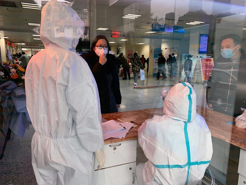 A woman speaks to hospital personnel wearing protective gear at No. 5 Hospital in Wuhan, China on Jan. 24, 2020. (Chris Buckley/The New York Times)