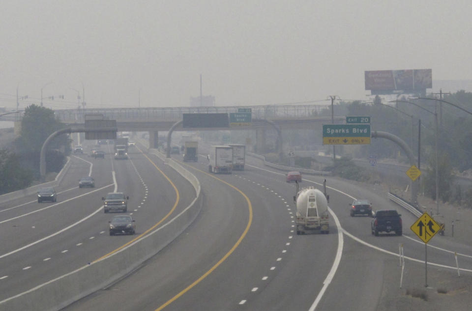 "FILE - In this Wednesday, Aug. 19, 2020. file photo, smoke from California wildfires up to 200 miles away obscures the view of traffic traveling on Interstate 80, looking west in Sparks, Nev. Local schools canceled all outdoor activities as the air quality index approached the ""very unhealthy"" category for the general population Wednesday afternoon. (AP Photo/Scott Sonner)"