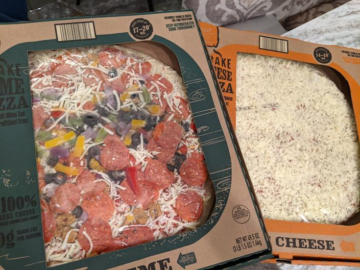 two Mama Cozzi's pizza in their original cardboard boxes