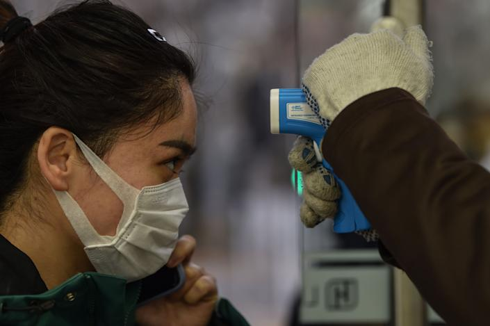 A worker checks the temperature of a customer at the entrance of a supermarket in Shanghai on February 26, 2020. - China on February 26 reported 52 new COVID-19 coronavirus deaths, the lowest figure in more than three weeks, bringing the death toll to 2,715. (Photo by Hector RETAMAL / AFP) (Photo by HECTOR RETAMAL/AFP via Getty Images)