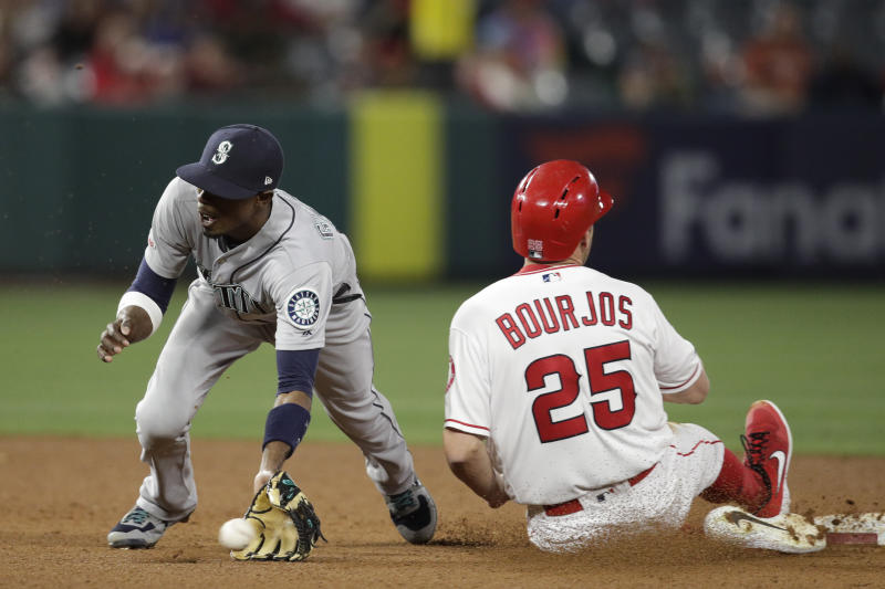 Seattle Mariners' Dee Gordon, left, misses the throw as Los Angeles Angels' Peter Bourjos steals second base during the fourth inning of a baseball game Thursday, April 18, 2019, in Anaheim, Calif. (AP Photo/Jae C. Hong)